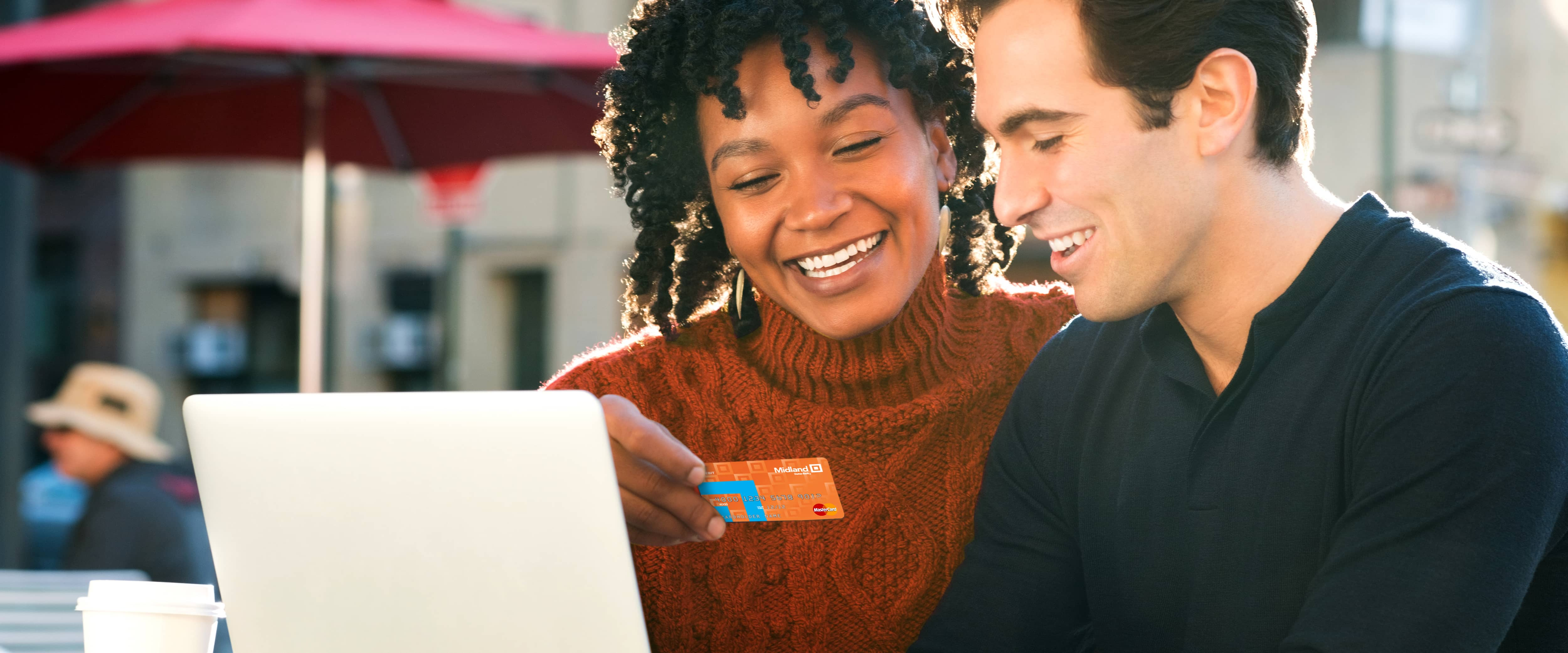 Smiling couple holding a Midland Debit Card while using laptop