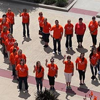 midland employees standing in heart in Midland orange shirts