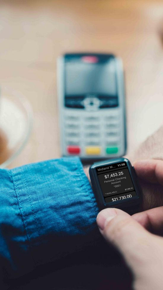 Man looking at his smartwatch with Midland banking on screen