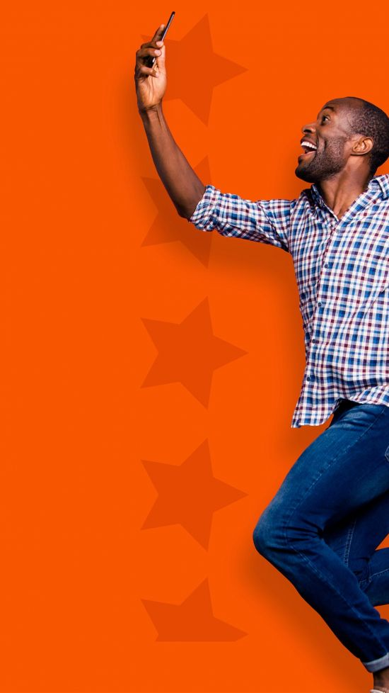 Black man holding cellphone and jumping in front of an orange background