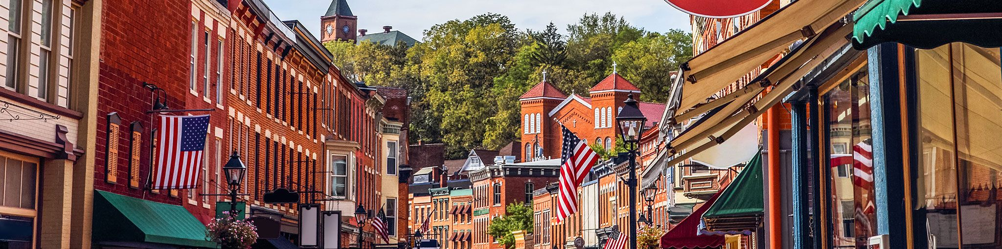 Small town street lined with brick buildings and American flags