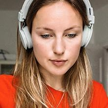 Caucasian woman looking at computer with headphones on
