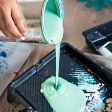 person pouring seafoam green paint into a paint tray
